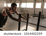man pushing sled in cross... | Shutterstock . vector #1014402259