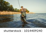 the fisherman is holding a fish ... | Shutterstock . vector #1014409240