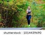 woman running in the autumn park | Shutterstock . vector #1014439690