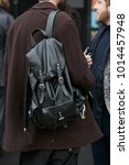 Small photo of MILAN - JANUARY 15: Man with black leather backpack and brown coat before Pal Zileri fashion show, Milan Fashion Week street style on January 15, 2018 in Milan.