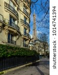 Small photo of Eiffel Tower with the turning of a street in the fashionable district of the 7th district of Paris. FRANCE - January 27th, 2018