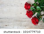 Stock photo red roses on wooden background 1014779710