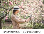 Small photo of Beautiful stylish caucasian woman making selfie in blossom magnolia garden.
