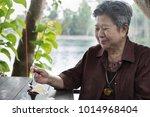 elder senoir eating chocolate... | Shutterstock . vector #1014968404