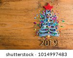 Small photo of Sigh symbol Christmas Tree from a lot colorful confetti, lace and red star toy on old retro vintage style wooden texture background Empty copy space for inscription Idea of merry new year 2019 holiday