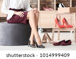 young woman trying on shoes in... | Shutterstock . vector #1014999409