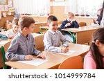 children taking an exam | Shutterstock . vector #1014999784