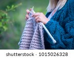 Small photo of Knitting on knitting. Hands close-up knitting on knitting needles, gray wool knit against the backdrop of a natural garden. Needlework in the garden.
