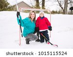 mother and son playing hockey | Shutterstock . vector #1015115524
