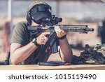 Man shooting assault style rifle at shooting range in desert resting on bench front