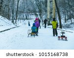 Small photo of kids rid on sleigh in winter day in city park