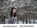 girl blows away the snow with... | Shutterstock . vector #1015204969