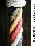 Small photo of Color Rope Design White Knot Red Green Yellow Purple Material Braided Entwine Twist Cross Texture Wood Background