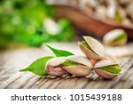 Small photo of Pistachios nuts on wooden table. Pistachio detail. Pistachio in wooden bowl in background with green leaves.
