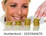 woman with coin stack while... | Shutterstock . vector #1015464670