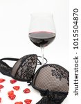 Small photo of seductive black lingerie bra in front of a red wine glass and red hearts - romantic seduction at the valentines day
