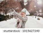 beautiful girl throws snow in a ... | Shutterstock . vector #1015627240