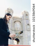 Small photo of Cheerful female traveler on trip to Europe.Female tourist holding a map in her hands,sightseeing landmarks around capital of Portugal.Exited woman standing in front of historical landmark,Pena palace