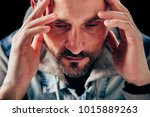 Small photo of Handsome man holding head in hands. Having problems with libido.