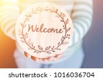 Small photo of WELCOME CONCEPT.Women holding welcome word wooden board at home.