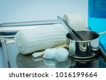 Small photo of Wound care dressing set on stainless steel plate. Cotton ball with alcohol, cotton stick, surgical tape, forceps and conform bandage.