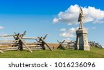 A stone monument of a civil war soldier stands before a wooden split rail fence as it marks the location of Antietam National Battlefield in Sharpsburg, Maryland