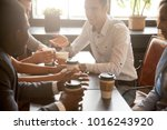 Small photo of Multi ethnic group of happy friends drinking coffee in paper cups together in cozy cafe, diverse multiracial african and caucasian young people talking sharing table having fun at coffeehouse meeting