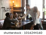 Small photo of Happy couple get acquainted with multiracial people coming at meeting in cafe, young man introducing handshaking african guy from diverse friends group, new acquaintance and making first impression