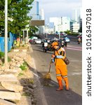 Small photo of JAKARTA, INDONESIA - DECEMBER 14, 2017: Unidentified Jakarta city cleaners (Pasukan Oranye) sweep dirt on the side of the highway.