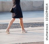 Small photo of girl is walking stride on the summer sunny city