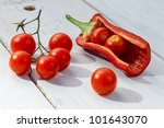 Fresh tomatoes and peppers on a board in the garden - stock photo