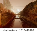 Small photo of small river with bridge at night in achinese city