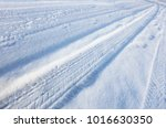 Small photo of car-ridden road covered with snow drifts, winter