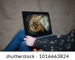 young woman trades bitcoin on... | Shutterstock . vector #1016663824