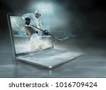 Small photo of Caucassian ice hockey Players in dynamic action in a professional sport game play on the laptop in hockey under stadium lights.