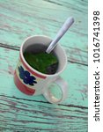 Small photo of Mug of water and tea leaves with a spoon standing on a weary painted turquoise table