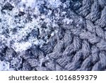 snowflakes laying on woolen... | Shutterstock . vector #1016859379