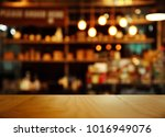 Stock photo top of nature wood with blur lamp light bar or club cafe background 1016949076