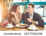 the happy man and woman eating...   Shutterstock . vector #1017036238