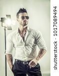 Small photo of Young macho in formal shirt and sunglasses holding cigarette posing confidently in studio.