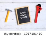 Small photo of Top view of hammer,wrench and blackboard written with 'BUILD YOUR FUTURE' on white wooden background.