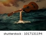 Small photo of musician holding guitar above water
