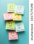 Small photo of Day of week and face expression. Colored stickers on a blue background