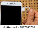 Small photo of Fingers holding a cellphone SIM card and inserting Nano Sim tray into the hole