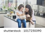 young mother cooking with their ... | Shutterstock . vector #1017250390