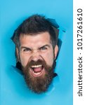 angry male face through hole in ... | Shutterstock . vector #1017261610