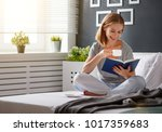 Happy Young Woman Reads Book...