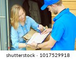 smiling delivery man in blue... | Shutterstock . vector #1017529918