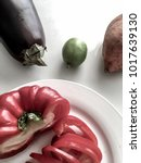 Small photo of Sliced capsicum red pepper with sweet potato, lime and eggplant aubergine ready to be cooked. Viewed from above against a white marble table