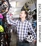 vigorous man in bicycle shop... | Shutterstock . vector #1017787243